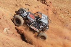 Voiture bleue mettant la colline sous tension raide, donnant un coup de pied le sable et la poussière Photographie stock libre de droits