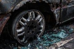 Voiture brûlée sur la route Pneu et verre fondu brûlés Image stock