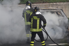 voiture brûlante avec des sapeurs-pompiers images stock