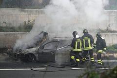 voiture brûlante avec des sapeurs-pompiers images libres de droits