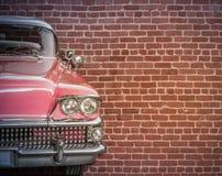 Voiture classique contre le mur de briques rouge Image stock