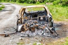 Voiture complètement brûlée sur la route de campagne Images stock