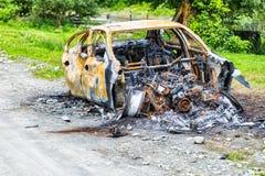Voiture complètement brûlée sur la route de campagne Photos stock