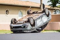 Voiture d'accidents retournée au milieu de la rue Photographie stock