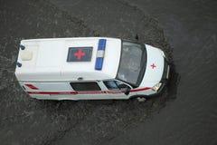 Voiture d'ambulance passant par la route inondée image stock