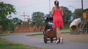 Voiture d'enfant de marche de jeune mère dans la position de parc de ville portant la robe rouge lumineuse avec les jambes nues banque de vidéos