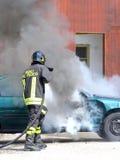 Voiture d'incident avec de la fumée noire et un sapeur-pompier italien avec du Th photographie stock libre de droits