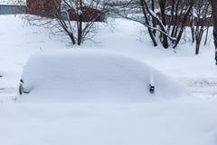 Voiture dans une congère après la chute de neige importante photos stock