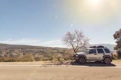 voiture 4x4 de côté de route en montagnes Photographie stock libre de droits