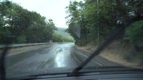 Voiture de conduite sous la pluie sur route humide Temps pluvieux à travers la fenêtre de la voiture banque de vidéos