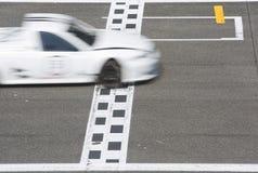 Voiture de course croisant la ligne d'arrivée Images libres de droits