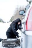 Voiture de défaut pendant l'hiver Jeune belle fille essayant de réparer t Photographie stock