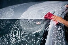 Voiture de lavage utilisant l'éponge nanoe avec la mousse Photographie stock libre de droits