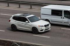 Voiture de luxe BMW blanc expédiant sur la route vide Photographie stock
