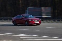 Voiture de luxe Mazda rouge expédiant sur la route vide Images libres de droits