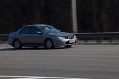 Voiture de luxe Subaru expédiant sur la route vide Photographie stock libre de droits