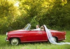 Voiture de mariage avec des jeunes mariés Images stock