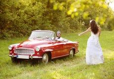 Voiture de mariage avec des jeunes mariés Photo stock