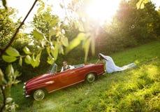 Voiture de mariage avec des jeunes mariés Photographie stock