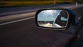 Voiture de miroir gauche sur une route image libre de droits