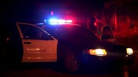 Voiture de police avec des lumières clignotant au barrage de route banque de vidéos
