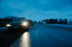 Voiture de sport noire sous la pluie à la route de nuit Photographie stock