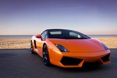 Voiture de sport orange sexy luxueuse près de plage Image libre de droits