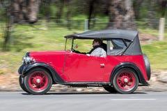 Voiture de tourisme 1937 d'Austin 7 conduisant sur la route de campagne Photo libre de droits