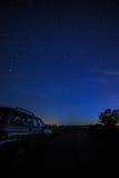 Voiture de touristes sur le ciel étoilé de fond et le chemin laiteux Images stock