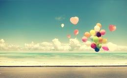Voiture de vintage avec le ballon de coeur sur le ciel bleu de plage Photo libre de droits