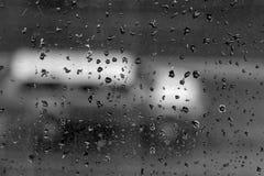 Voiture derrière une fenêtre sale avec des baisses Photographie stock libre de droits