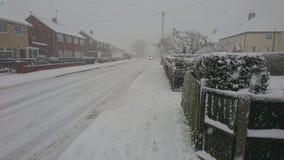Voiture descendant une rue neigeuse de village Photo libre de droits