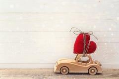 Voiture en bois de jouet avec le coeur sur le toit sur une table en bois Placez f Photo stock