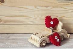 Voiture en bois de jouet avec les coeurs rouges sur un fond des conseils en bois Photo stock