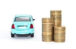 Voiture et pièces de monnaie sur un fond blanc Images stock