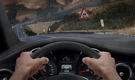 Voiture glissant sur une route sous la pluie À côté de la route est un signe pour la route glissante Pare-brise éclaboussé par pl images libres de droits