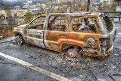 Voiture grillée étripée par Forest Fire image stock