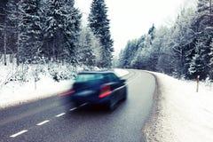 Voiture isolée sur la route dans le paysage d'hiver Photographie stock libre de droits