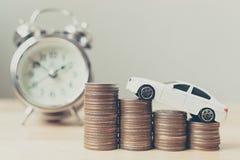 Voiture miniature blanche sur la croissance de pile de pièce de monnaie d'argent avec l'horloge Images libres de droits