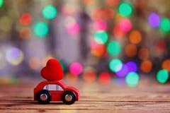 Voiture miniature portant un coeur rouge sur le toit Amour de concept de vacances Photo libre de droits
