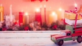 Voiture modèle avec des présents sur son toit et fond brouillé des bougies combinées avec la neige en baisse illustration stock