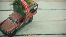 Voiture modèle avec l'arbre de Noël sur son toit combiné avec la neige en baisse banque de vidéos