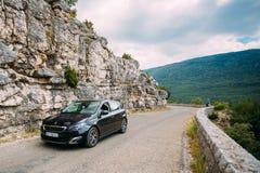 Voiture noire de Peugeot 308 de couleur sur le fond du Na français de montagne Images libres de droits