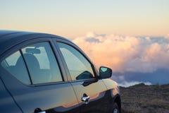 Voiture noire en montagnes au-dessus des nuages au coucher du soleil ou au lever de soleil Photo stock