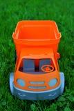 Voiture orange et grise de jouet sur l'herbe verte image libre de droits