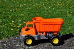 Voiture orange et grise de jouet sur la pierre photo stock