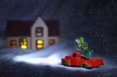 Voiture rouge authentique de Santa Claus avec un arbre de Noël près de la maison Paysage de Noël de nuit avec la neige en baisse photos stock
