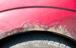 Voiture rouge corrodée endommagée avec haut étroit rayé de peinture et de rouille photographie stock