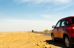 Voiture rouge d'apparence de tir sur un long tronçon de route vide dans Rann de Kutch Goudjerate photographie stock libre de droits