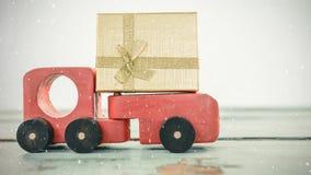 Voiture rouge de jouet avec un présent combiné avec la neige en baisse banque de vidéos